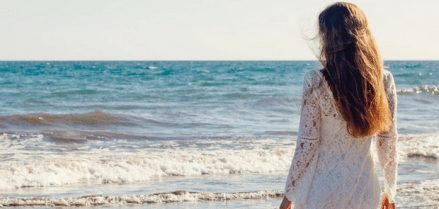 Girl on beach staring at the ocean