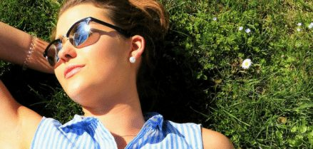 Girl laying in grass with sunglasses looking into the sun