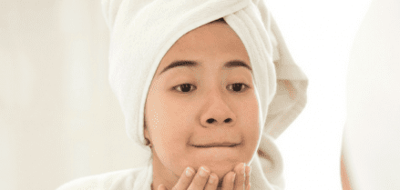 Girl washing face with a towel on her head