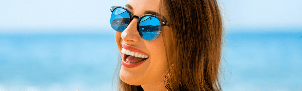 Woman smiling with sunglasses and sunscreen on her nose