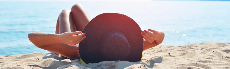 Woman laying on beach with hat on