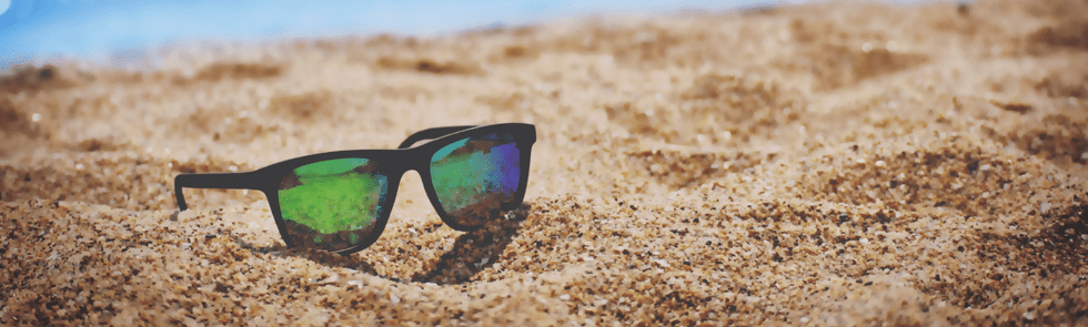 Sunglasses in sand on the beach