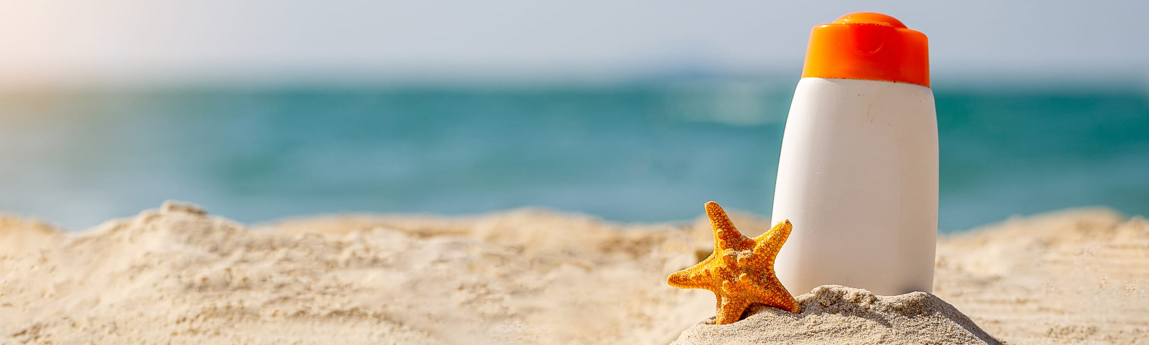 Sunscreen bottle at the beach with a starfish
